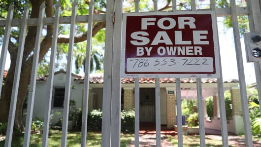 A for sale sign is seen in front of a home in Miami.