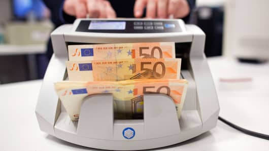 A worker puts 50 euro bank notes into a counting machine.