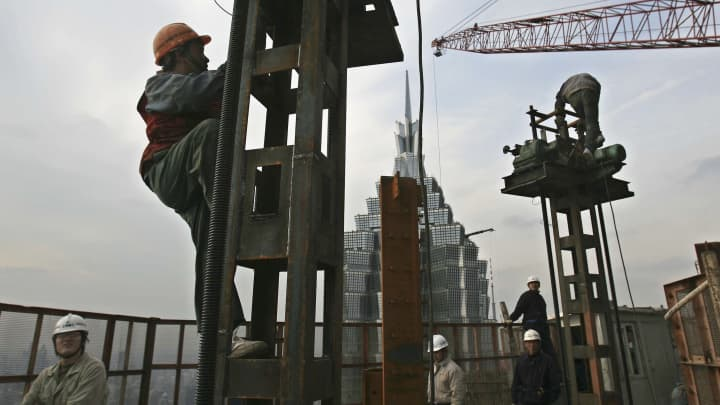 Skyscraper with scaffolding and workers, building
