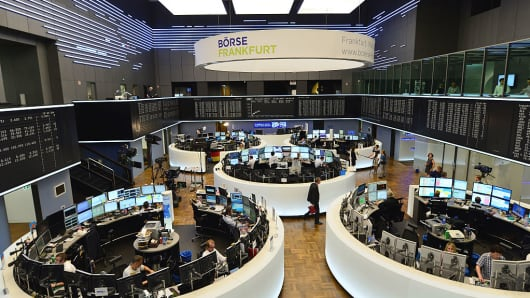 Traders sit at their desk at the Frankfurt Stock Exchange.