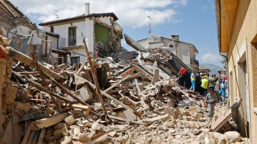 People and rescuers stand next collapsed buildings following an earthquake in Amatrice, central Italy, August 24, 2016.