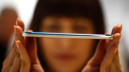 An employee shows the curved screen of a Galaxy S6 Edge smartphone device