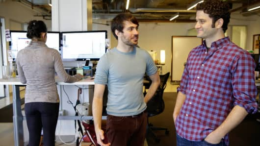 Asana co-founders Justin Rosenstein, center, and Dustin Moskovitz, right, pose for photos at the company's headquarters in San Francisco.