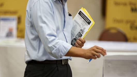 A job seeker looks at brochures during a Choice Career Fair in Los Angeles.