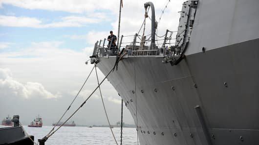 An armed watchman stands on the prow of the USS Nitze, moored at the Mocangue Island's Brazilian Navy base in Brazil, on April 27, 2011.