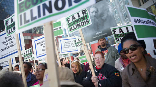 Demonstrators protesting the state of the Illinois budget stalemate rally in the Loop before marching to the Chicago Board of Trade Building, where they blocked entrances on November 2, 2015.