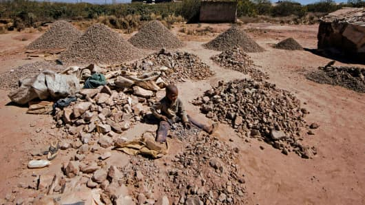 A child breaks rocks extracted from a cobalt mine in Lubumbashi, DRC on May 23, 2016.