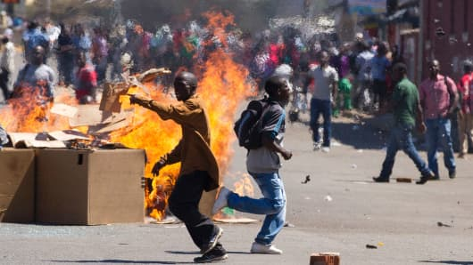 Zimbabwe opposition supporters set up a burning barricade as they clash with police during a protest march for electoral reforms on August 26 in Harare.