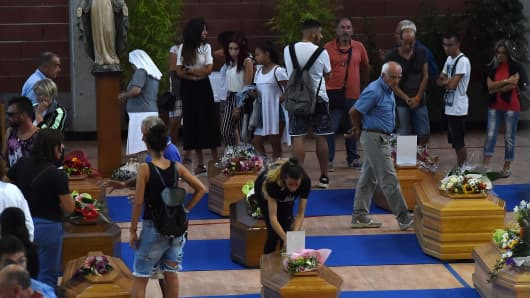 Relatives fill an auditorium with coffins ahead of funerals in Ascoli Piceno, Italy, for the victims of the earthquake.