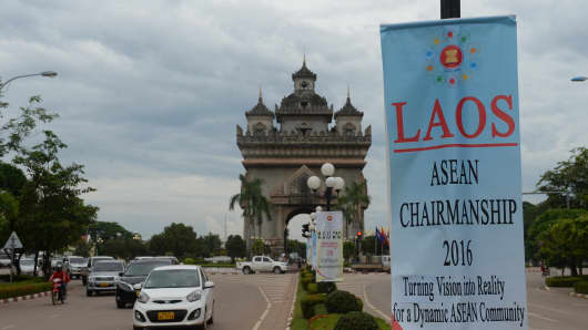Commuters ride past the Patuxay tower and a sign for the 49th annual ministerial meeting of the Association of Southeast Asian Nations in the Laos capital of Vientiane on July 23.