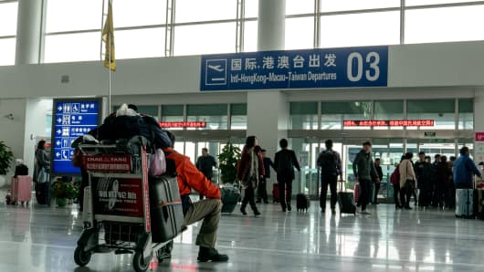 A member of a tourist group rests in the departure hall in the Xiaoshan Airport in Hangzhou.