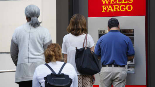 Customers wait in line for an ATM outside of a Wells Fargo bank branch in Los Angeles.