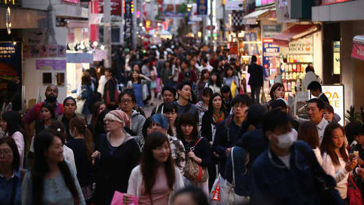 People walk along a shopping street in the Harajuku area of Tokyo, Japan.