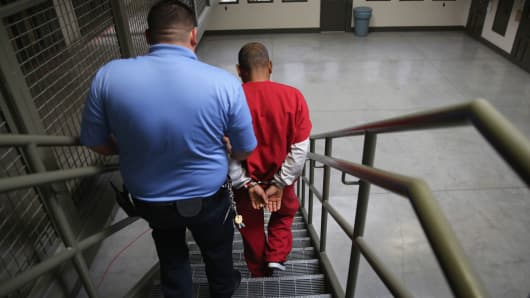 A guard escorts an immigrant detainee from his 'segregation cell' back into the general population at the Adelanto Detention Facility, managed by GEO Group.
