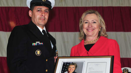 Secretary of State Hillary Rodham Clinton presents a letter of congratulations and signed photo to Chief Culinary Specialist Oscar Flores during his retirement ceremony aboard the multi-purpose amphibious assault ship USS Makin Island on April 1, 2011.