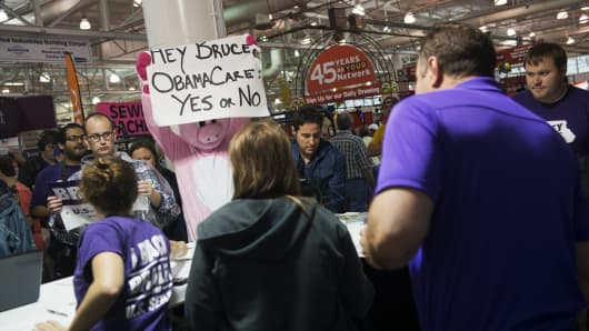 A heckler holds a sign taunting Senate candidate Rep. Bruce Braley, D-Iowa, about the Affordable Care Act at the 2014 Iowa State Fair in Des Moines, Iowa, August 7, 2014.