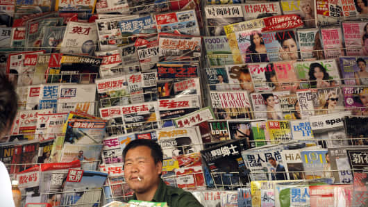 A newspaper vendor talks to a customer at his newsstand on a street in Beijing.