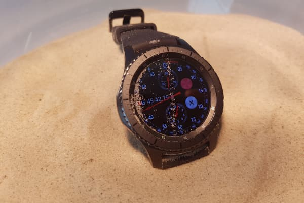 "Samsung demonstrates the ruggedness of the Gear S3 ""Frontier"" by putting it in sand at a demo at the IFA consumer electronics show in Berlin, 2016."