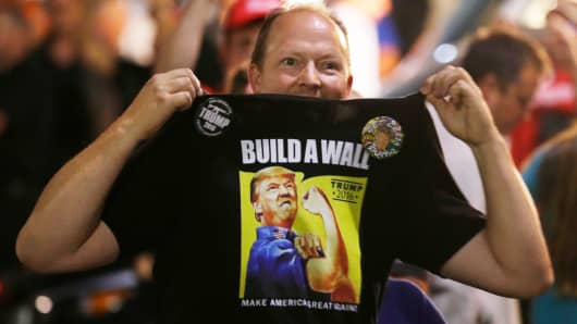 "A supporter of Republican presidential candidate Donald Trump holds up his shirt, bearing the Trump slogan ""Build a Wall,"" following a rally for Trump in Everett, Washington last August."
