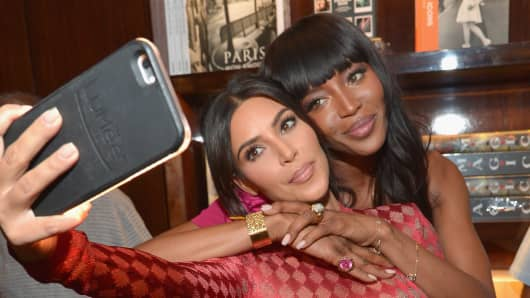 TV personality Kim Kardashian and model Naomi Campbell take a selfie during the Los Angeles launch of 'Naomi' at Taschen Beverly Hills on April 28, 2016 in Beverly Hills, California.