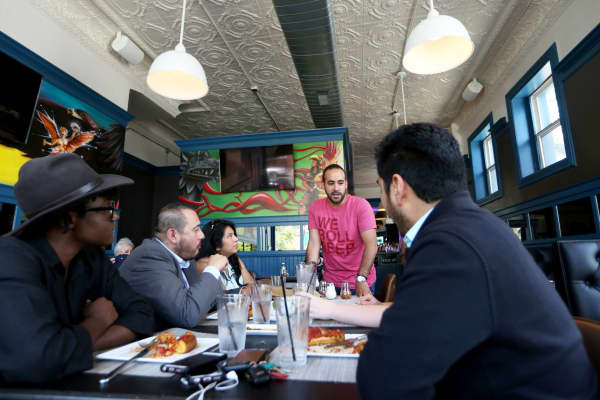 Jos Saldana, director of Gino's East Mexico, speaks with patrons at Gino's East Pilsen in Chicago.