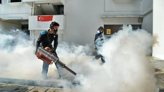 Pest control workers fumigate the drainage at a Macpherson housing estate in Singapore on August 31, 2016.