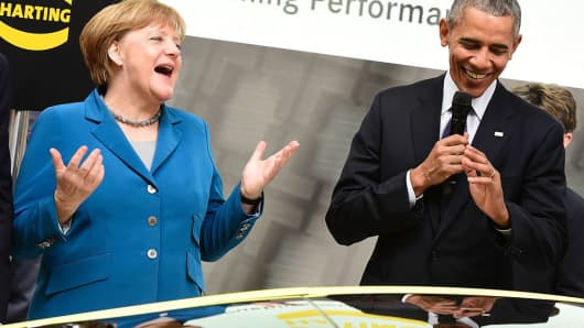 US President Barack Obama (R) and German Chancellor Angela Merkel share a laugh at the booth of Harting technology group as they tour the Hanover industrial Fair in Hanover, central Germany, on April 25, 2016.