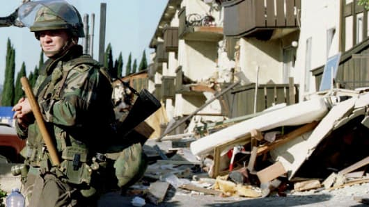 A National Guardsman stands guard outside the ruins of the Northridge Meadows Apartments where on January 17, 1994 an earthquake rocked Southern California.