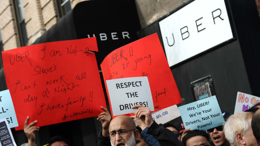 Uber drivers hold up protest signs outside the ride sharing company's offices in demonstration against the recent decision to cut fares, in the New York City borough of Queens, NY
