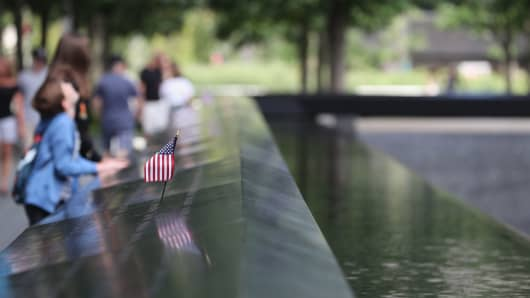 A young boy looks up to One World Trade Center next to a US flag at the the 9/11 memorial site