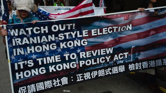 Activists holding a banner and US flags march during a rally against the banning of pro-independence candidates in the upcoming legislative council elections, in Hong Kong on August 21, 2016. Hundreds of protesters on August 21 marched over the Hong Kong government's ban on pro-independence candidates from running in the city's upcoming legislative election, as fears grow over Beiji