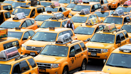 Yellow taxi cabs line up outside the Delta Terminal at LaGuardia Airport in Queens, New York.