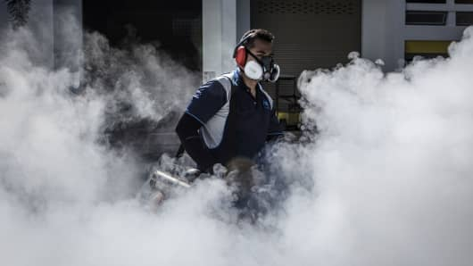 A pest control worker fumigates the grounds of a apartment block in Aljunied on September 3, 2016 in Singapore.