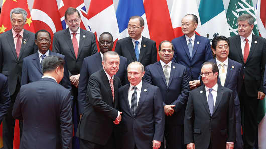 Russian President Vladimir Putin shakes hands with Turkish President Recep Tayyip Erdogan before a group photo at the Hangzhou International Expo Center to the G20 Summit on September 4, 2016.