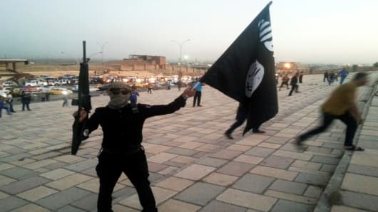 A fighter of the Islamic State of Iraq and Syria, or ISIS, holds a flag and a weapon.