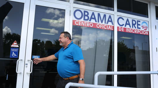 A person walks into the UniVista Insurance company office where people are signing up for health care plans under the Affordable Care Act, also known as Obamacare, in Miami, Florida.