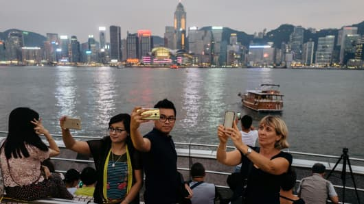Tourists take photographs with their smartphones on the waterfront in the Tsim Sha Tsui district in Hong Kong.