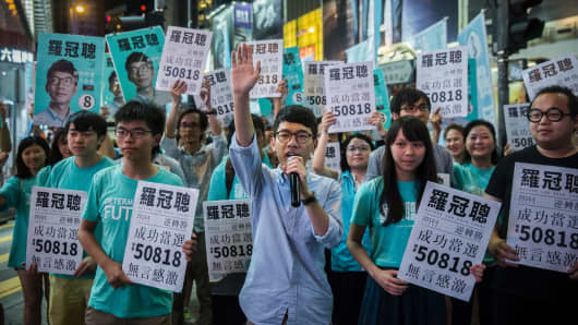 Nathan Law (C) speaks at a rally with Joshua Wong (centre L) and supporters following the former's Legislative Council election win in Hong Kong on September 5, 2016.