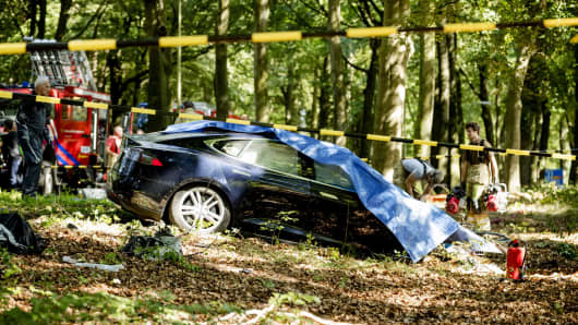 Rescue workers proceed with caution around the spot where a Tesla slammed into a tree in Baarn, Netherlands, on September 7, 2016.