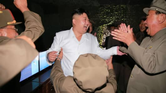 An undated picture released from North Korea's official Korean Central News Agency (KCNA) on August 25, 2016 shows North Korean leader Kim Jong-Un (C) laughing as he inspects a test-fire of strategic submarine-launched ballistic missile at an undisclosed location.