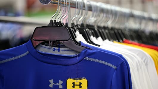 Under Armour clothing on a display in a sporting good store.