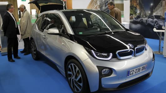 Visitors look at a BMW i3 electric automobile during the Paris Motor Show on October 14, 2014 in Paris, France
