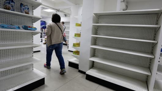 A woman walks past empty shelves at a drugstore in Caracas, Venezuela.