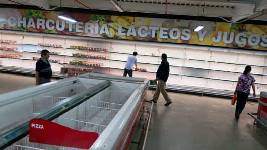 People walk at the refrigerated foods section inside a Makro supermarket in Caracas, Venezuela.