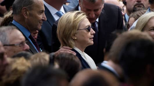 New York City Mayor Bill de Blasio speaks to US Democratic presidential nominee Hillary Clinton during a memorial service at the National 9/11 Memorial September 11, 2016 in New York.