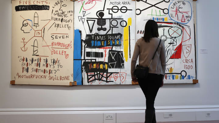 visitor stands in front of a painting by Jean-Michel Basquiat entitled 'Five Fish Species,' on January 31, 2013 in London, England.