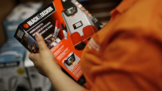An employee holds a Stanley Black & Decker Inc. cordless drill while helping a customer at a Home Depot Inc. store in New York.