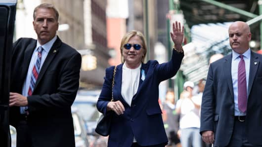 Hillary Clinton waves as she leaves her daughter's New York apartment building after resting there on Sept. 11, 2016.