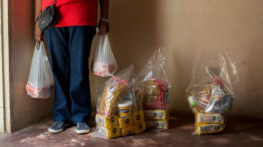 A Venezuela resident carries food in plastic bags in the Catia neighborhood on the outskirts of Caracas, Venezuela