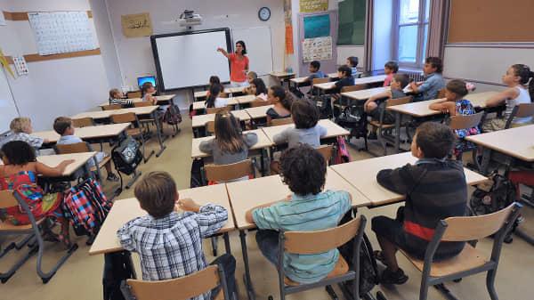 Teacher with students, chalkboard